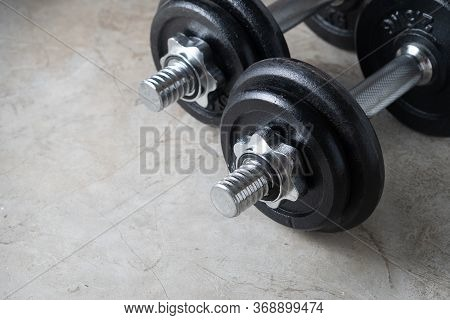 Dumbbells For Muscle Building Exercise Placed On Cement Floor With Copyspace.body Workout In The Gym