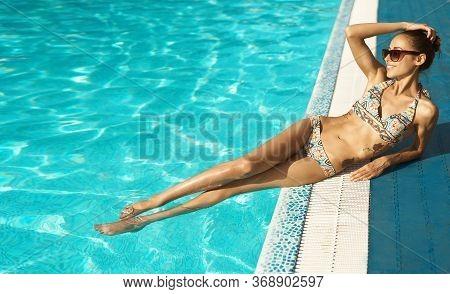 Tanned Woman With Amazing Slim Fitness Body In Bikini And Sunglasses Enjoying Pool Leisure And Sunba