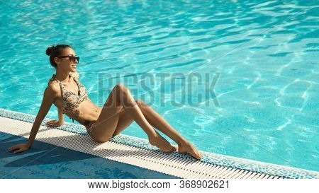 Pretty Girl With Tanned Sexy Body In Bikini And Sunglasses Posing Near Swimming Pool. Relaxing, Enjo