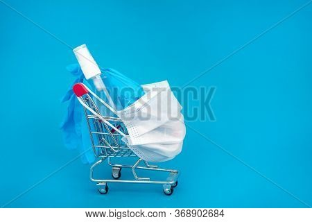 Medical Surgical Mask, Sanitizer Gel And Blue Lab Gloves In Shopping Trolley On Supply Of Virus Prot