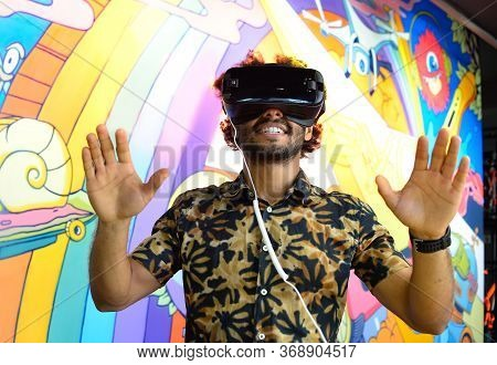 The Dark-skinned Cheerful Guy Plunged Into The Virtual World, Wearing Virtual Reality Glasses. Portr