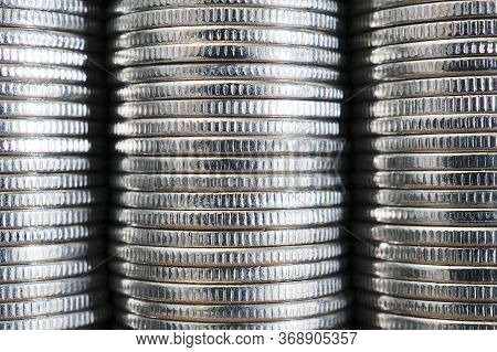 Background From Stacks And Edges Of Nickel White Coins Close-up. Textured Backdrop Or Wallpaper. 1 R