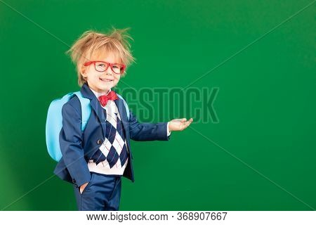 Bright Idea! Funny Child Student In Class. Happy Kid Against Green Chalkboard. Online Education And
