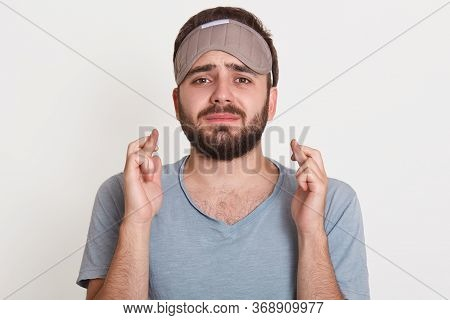 Portrait Of Pleading Upset Annoyed Man Looking Directly At Camera, Crossing His Fingers, Wearing Sle