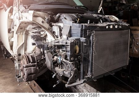 The Front Part Of The Car After An Accident In A Car Repair Service With A Disassembled Hood And Met