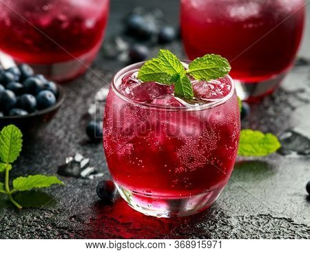 Refreshing Blueberry Cocktail With Ice And Mint On Rustic Black Table