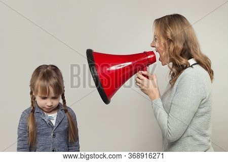 Child Abuse Concept. Parent Abusing Kid, Mother Shouting In Loudspeaker To Sad Daughter