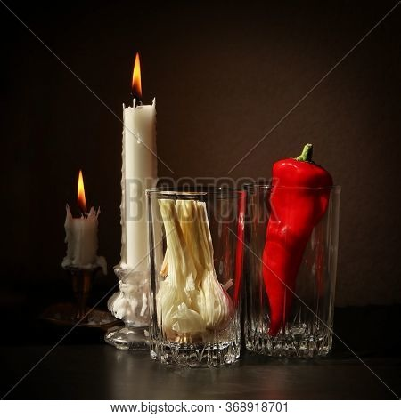 Still Life With Two Candlesticks With Burning Candles, Red Ramiro Pepper And Garlic Bulb In The Glas