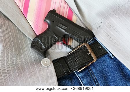 A Gun Tucked Into A Leather Belt So Close