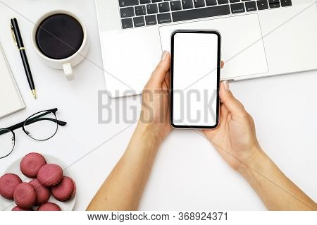 Mock Up Image Of Female Hand Holding And Using Black Mobile Phone With Blank Screen On Laptop Comput