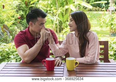 Cheerful Young Couple Holding Hands With Cup Of Coffee Or Tea While Sitting On Chair In The Garden A