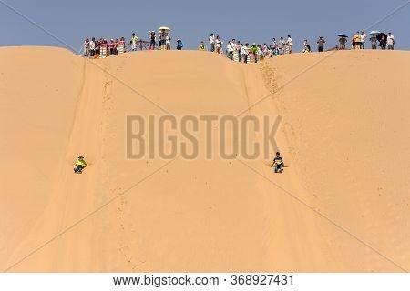 Kubuqi Desert, Inner Mongolia Province / China - July 31, 2016: People Sand Dune Sledging In Kubuqi