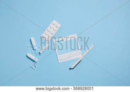 Menstrual Sanitary Tampon, Pain Pills During Menstruation On Blue Background, Feminine Calendar With