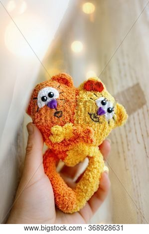 Love Cats Toy Knitted Two Red And Yellow Made Of Wool In Female Palm Against Background Of Yellow Ai