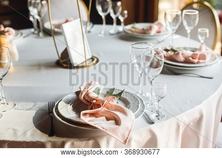 Close Up Festive Table Setting With Empty Wine Glasses And White Plate