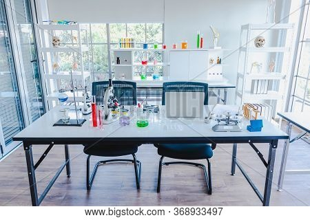 Glasswares And Skeleton At The Science Laboratory. The Multicolored Solution In A Glass Beaker On A