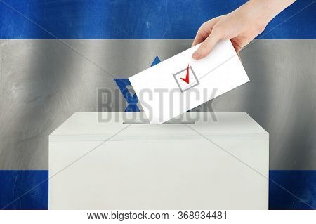 Israeli Vote Concept. Voter Hand Holding Ballot Paper For Election Vote On Polling Station