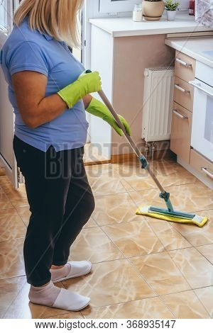 A Woman Washes The Floor Of Tiles In The Kitchen With A Mop. Cleaning Of The Apartment. Yellow Rag.