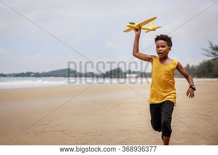 Happy Colored Boy And African American Boy Playing Yellow Toy Airplane And Running By Wearing Yellow