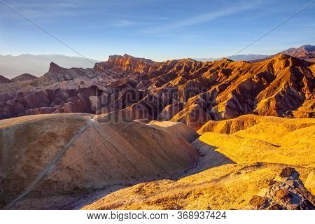 Zabriskie Point is part of the Amargosa Range. Death Valley in California, USA. Picturesque multicolor sunset. The concept of active, extreme and photo tourism