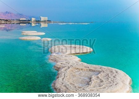 Israel. Azure sea water is full of healing salts. Small islets and path of salt in the water. Early morning at the resorts of the Dead Sea. Concept of ecological, medical and photo tourism