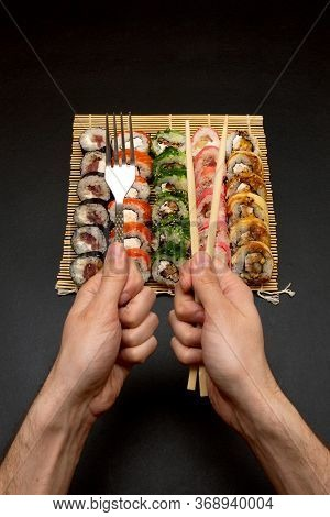 Chopsticks And Fork In Hand With Sushi On Black Background.