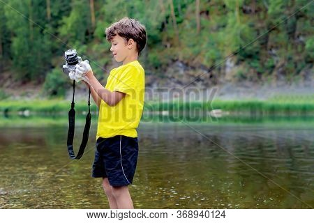 A Schoolboy Is Standing In Outdoor Near The Forest, Holding A Photo Camera In His Hands And Washing,