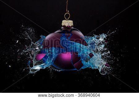 A Bauble Bursting Open Releasing Blue Liquid