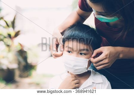Mother Take Care Son With Face Mask For Protection Disease Flu Or Covid-19 Outdoors, Mom Wearing On