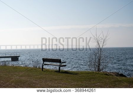 An Empty Bench Just Close To The Sea With The Oresund Bridge In The Fog In The Background
