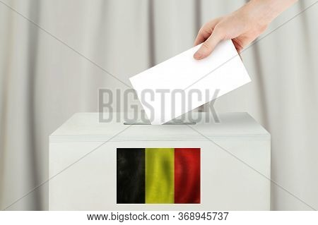 Belgian Vote Concept. Voter Hand Holding Ballot Paper For Election Vote On Polling Station