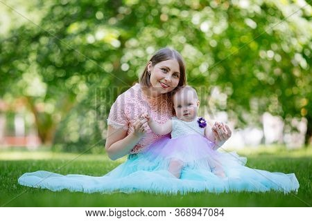 Happy Mother And Daughter In The Park. Beauty Nature Scene With Family Outdoor Lifestyle. Happy Fami