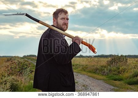 A Man With A Beard On His Shoulder A Spade Turned Around And Looks At The Background Of The Field On