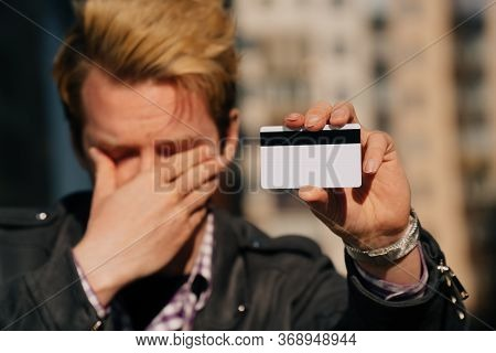 A Close-up Of A Young Man Cries, The Concept Of Credit Card Theft. Stole Cashless Money