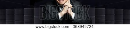 Happy Smiling Businessman With Crude Oil Barrels On Black Background. Crude Oil And Petroleum Indust