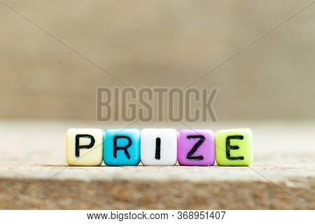 Colorful Bead With Black Letter In Word Prize On Wood Background