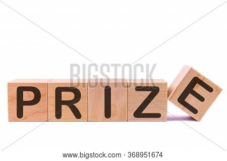 Word Prize Is Made Of Wooden Building Blocks Lying On The Table And On A Light Background. Concept.
