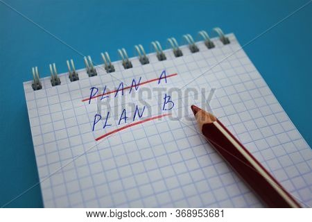 In A Spiral Notebook In A Cell Crossed Out With A Red Pencil Plan A, Underline Plan B. Red Pencil Is