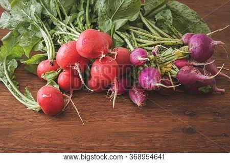Fresh Red And Purple Radishes On Wooden Table. Two Varieties Of Radishes, Close Up View Of Raw And H