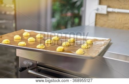 Bakery baker preparing bread cooking in the oven.Bakery close up holding a peel with freshly baked.A