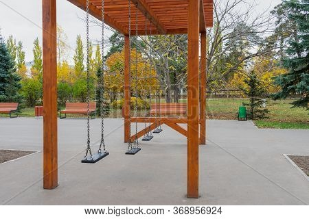 Empty Swings On Playground During Quarantine Or Beginning Or Ending Of School Semester.concept Of Ab