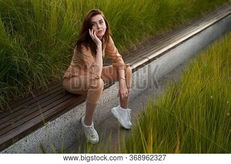 Young Beautiful Red Haired Gen Z Girl Wearing Slim Fitted Women Beige Khaki Coverall Overall Denim J