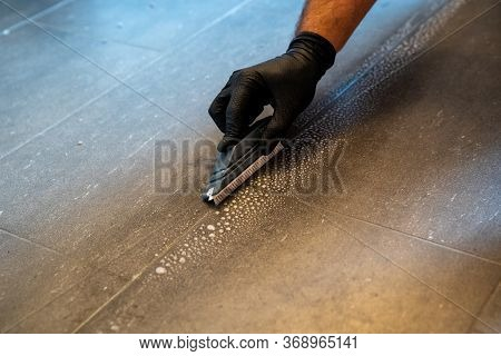 Professional Cleaner Cleaning Grout With A Brush Blade And Foamy Soap On A Gray Tiled Bathroom Floor