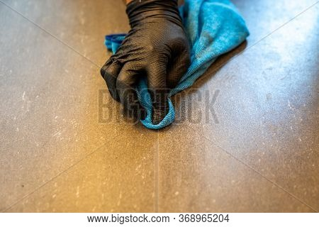 Close Up Of Professional Cleaner Cleaning Grout With A Blue Cloth Rag And Foamy Soap On A Gray Tiled
