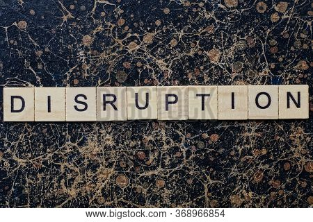 Gray Word Disruption From Wooden Letters In Black Font On A Brown Shabby Wall With A Pattern