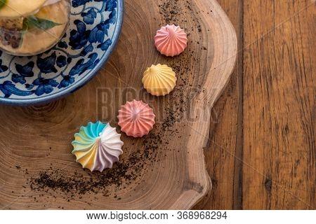 Colorful Meringues On Plate On Wooden Table. Rainbow Meringue Dessert. Top View