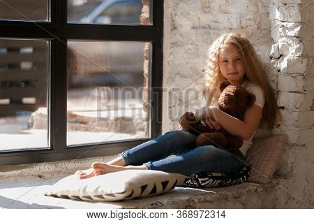 Beautiful Little Blonde Girl With Long Hair Sits Near Window With Pillows In A Bright White Bedroom