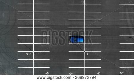 Top View On An Empty Parking Lots With One Blue Car. Aerial View Of Car Park.