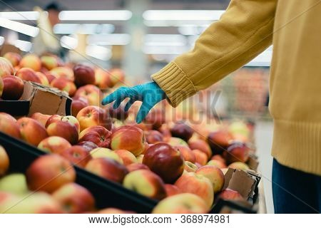 Buyer Is Picking Apples In The Store . Security Concept