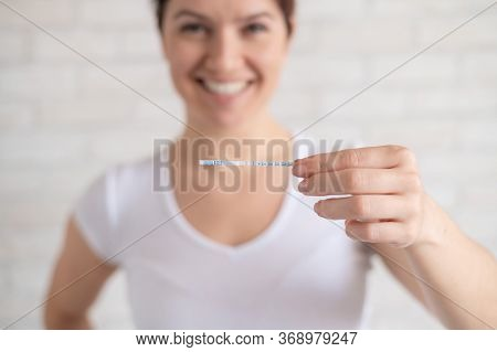 Happy Woman Shows A Positive Ovulation Test. The Concept Of Female Fertility And High Luteinizing Ho